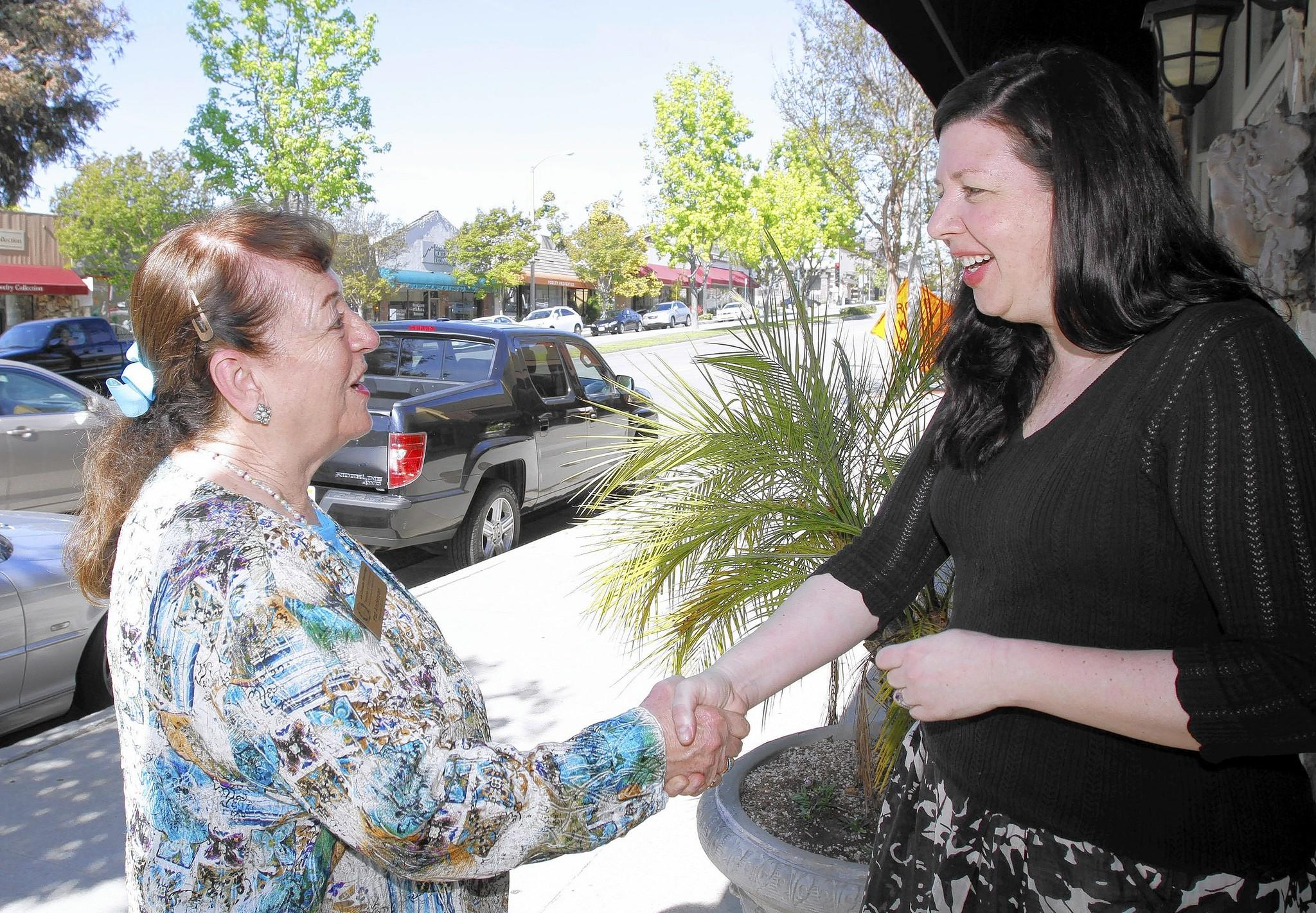 "La Cañada Flintridge Chamber of Commerce president Pat Anderson, left, talks about store-front parking problems with Chez owner Kerry Rasmussen, in front of Chez in La Cañada Flintridge on Tuesday, April 8, 2014. Anderson is this year's ""La Canadan of the Year."""