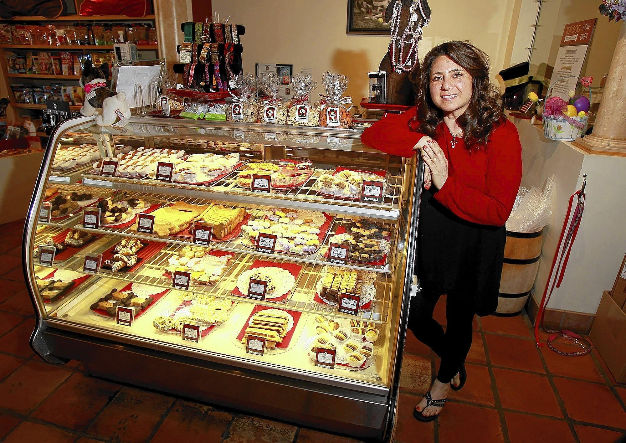 Karen Mahmalji stands next to a display case of baked tasty treats for dogs of all sizes at the Top Dog Barkery in Newport Beach.
