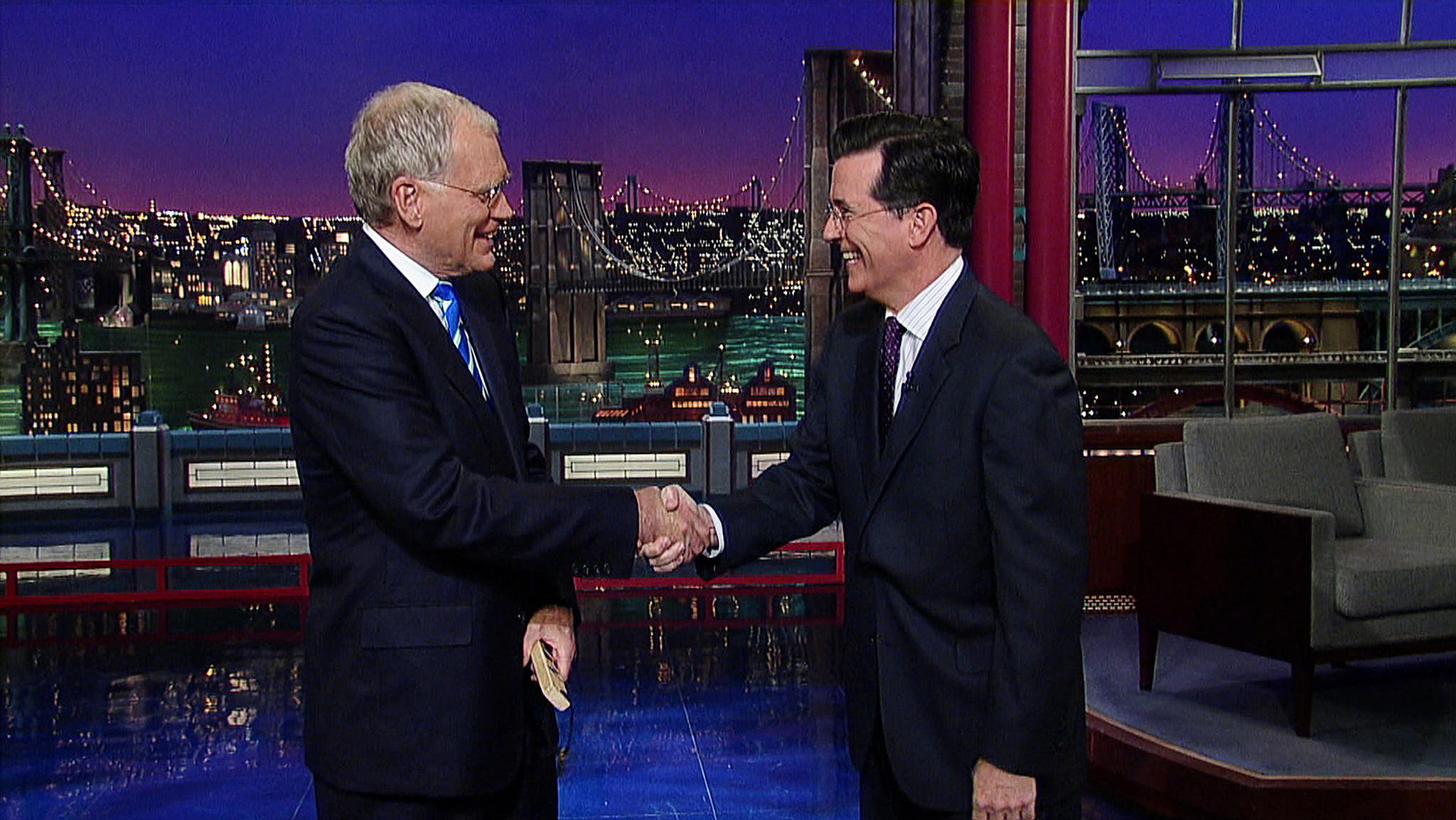"David Letterman shakes hands with fellow talk show host Stephen Colbert after Colbert comes by for a surprise visit on the ""Late Show"" in May 2011. CBS announced Thursday that Colbert will succeed Letterman as host when the latter steps down next year."