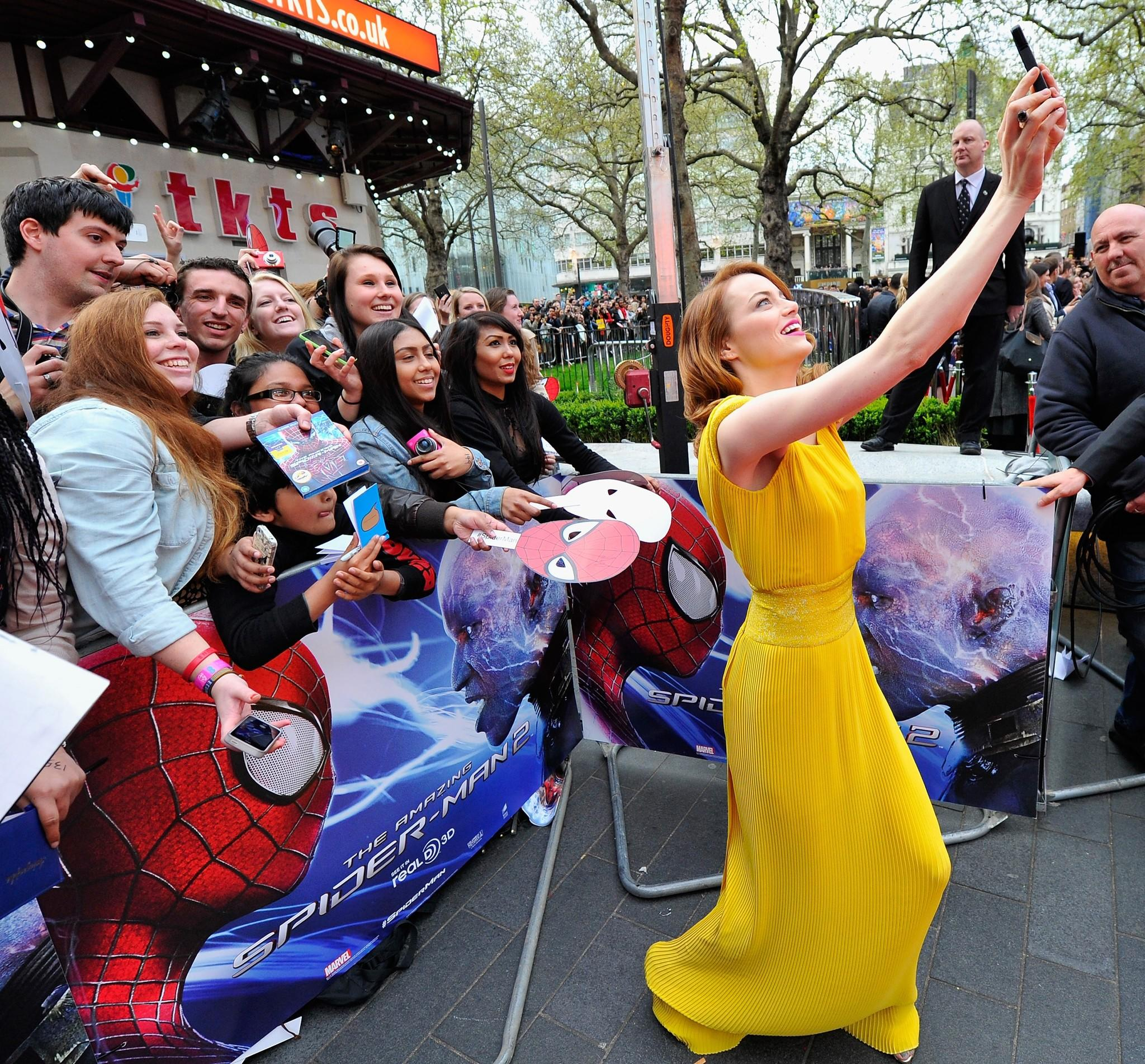 """Actress Emma Stone with fans as she attends """"The Amazing Spider-Man 2"""" world premiere at the Odeon Leicester Square in London."""