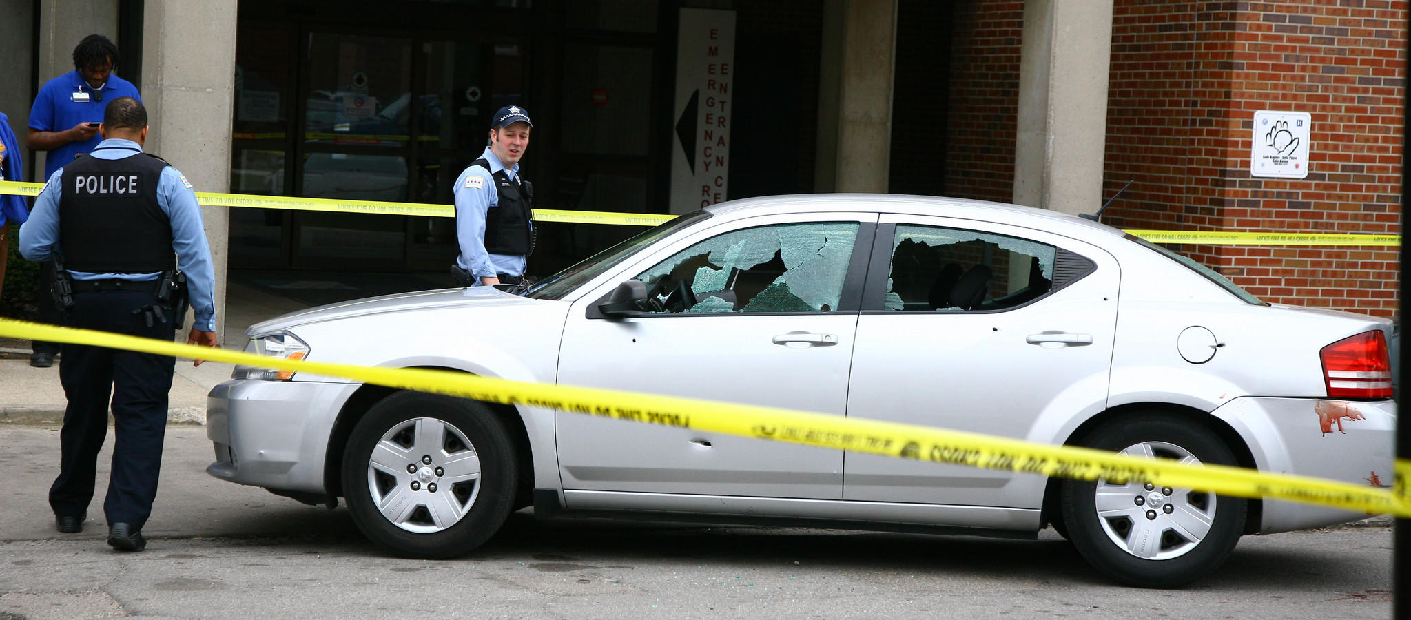 Chicago police officers look over a car riddled with bullet holes at South Shore Hospital after a shooting in the 7800 block of South Crandon Avenue.
