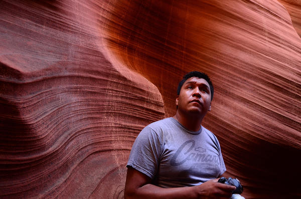 Navajo guide Raymond Chee inspects the light while leading a photo tour inside Upper Antelope Canyon, which lies on Navajo land near the Arizona-Utah border. Photo taken in 2013.