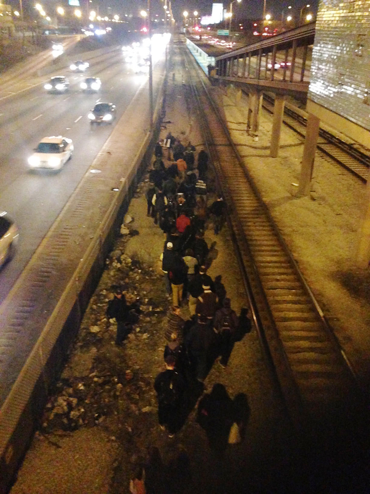 People walk along the Blue LIne tracks next to the Eisenhower Expressway following a derailment of a CTA train.