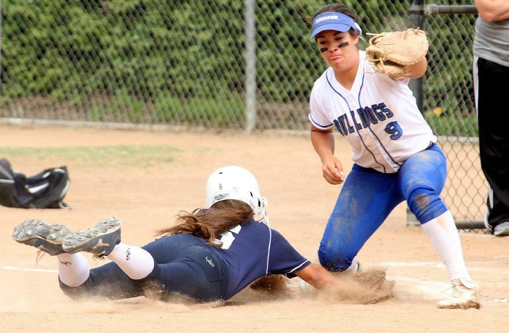 Burbank High's Julia Duarte catches the ball in a pickoff attempt against Crescenta Valley's Rachael Abboud, who dives safely back to first base in a Pacific League softball game at McCambridge Park in Burbank on Thursday. Burbank won the game 3-0. (Tim Berger/Staff Photographer)