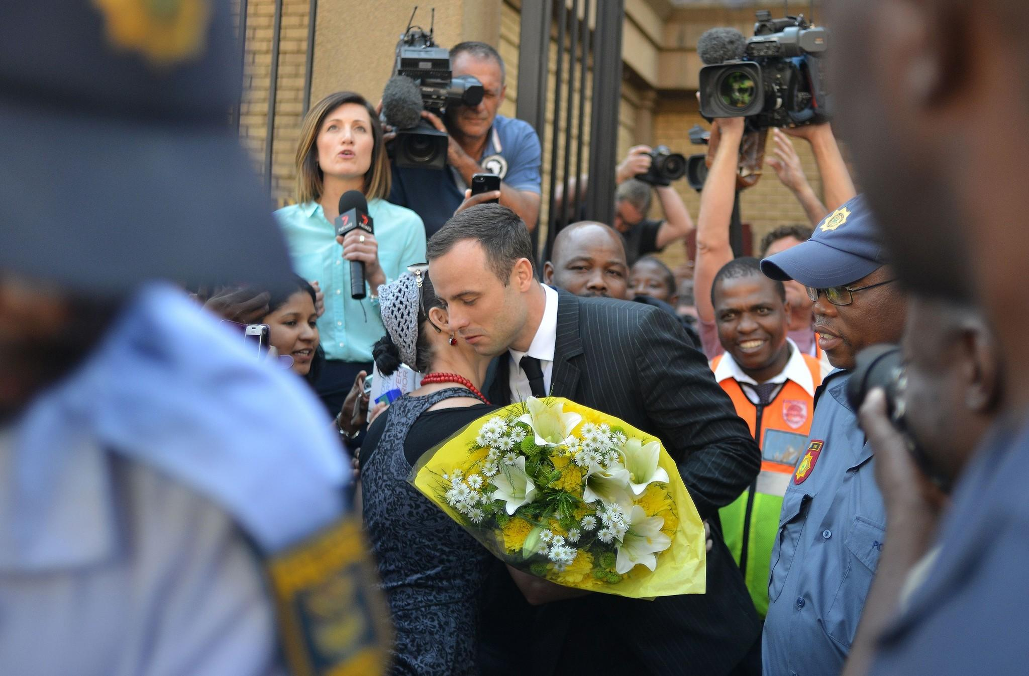 A woman hugs South African athlete Oscar Pistorius after handing him flowers as he leaves court in Pretoria on Friday.