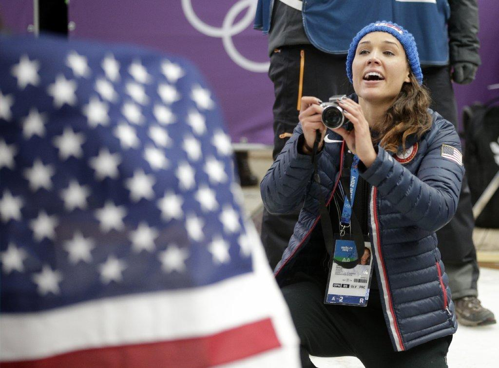 American bobsledder Lolo Jones takes pictures of her teammates after they won silver and bronze during the women's bobsled competition at the 2014 Olympics on Feb. 19.