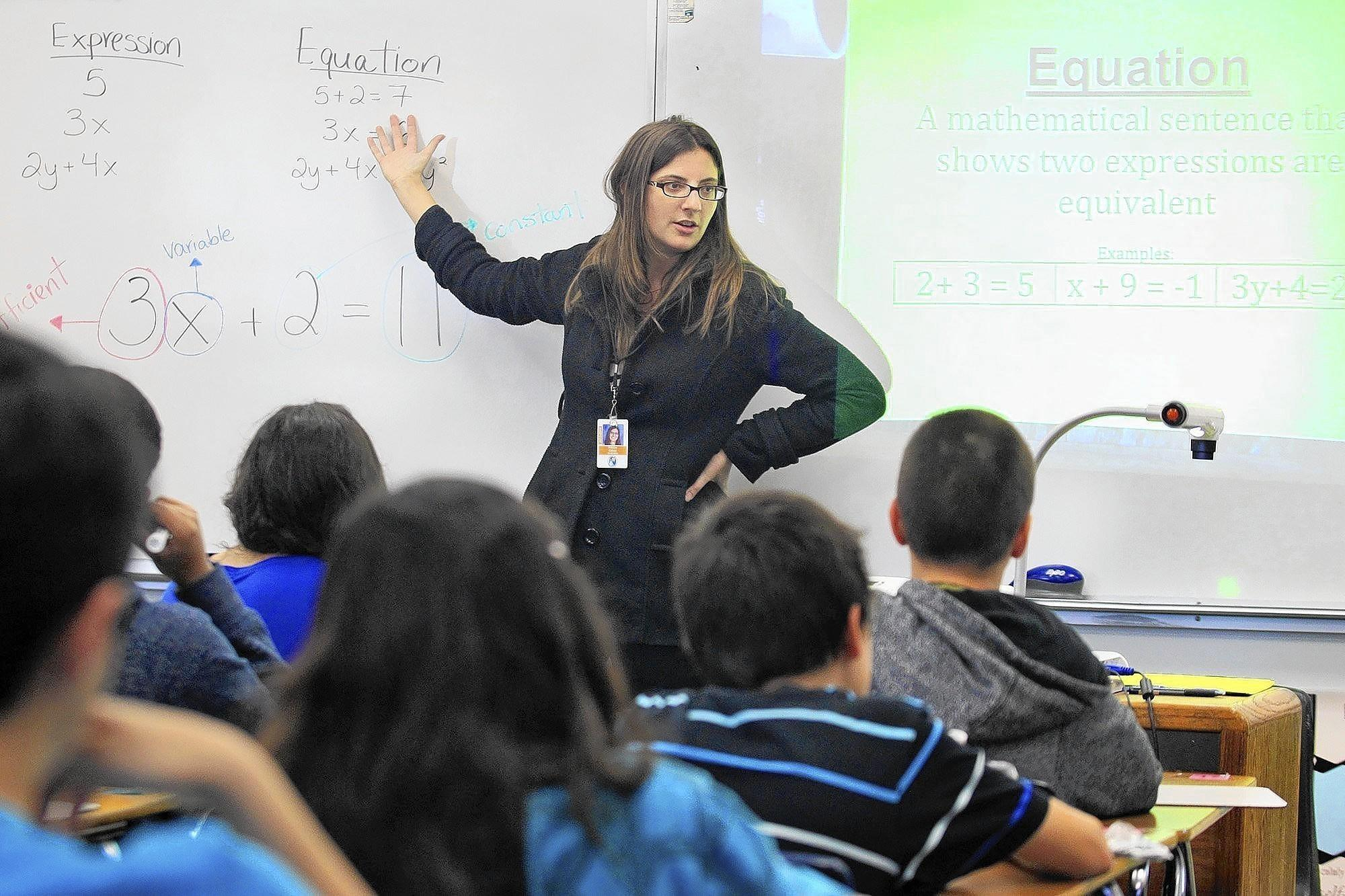 Math teacher Racine Cross instructs a class of seventh-graders during a class activity at Costa Mesa Middle School. Newport-Mesa is implementing new math pathways and strategies that align with new Common Core state standards in its middle schools this year. The new standards offer a more hands-on approach to learning.