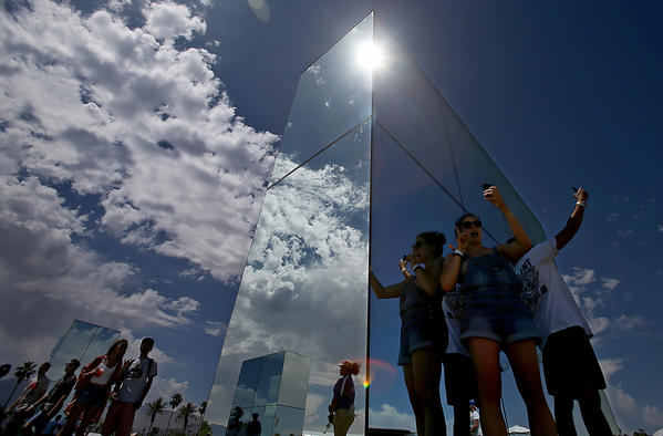 The sun reflects brightly on mirrored works of art as the gates open and participants take phone camera selfies on the first day of the Coachella Valley Music and Arts Festival on Friday.