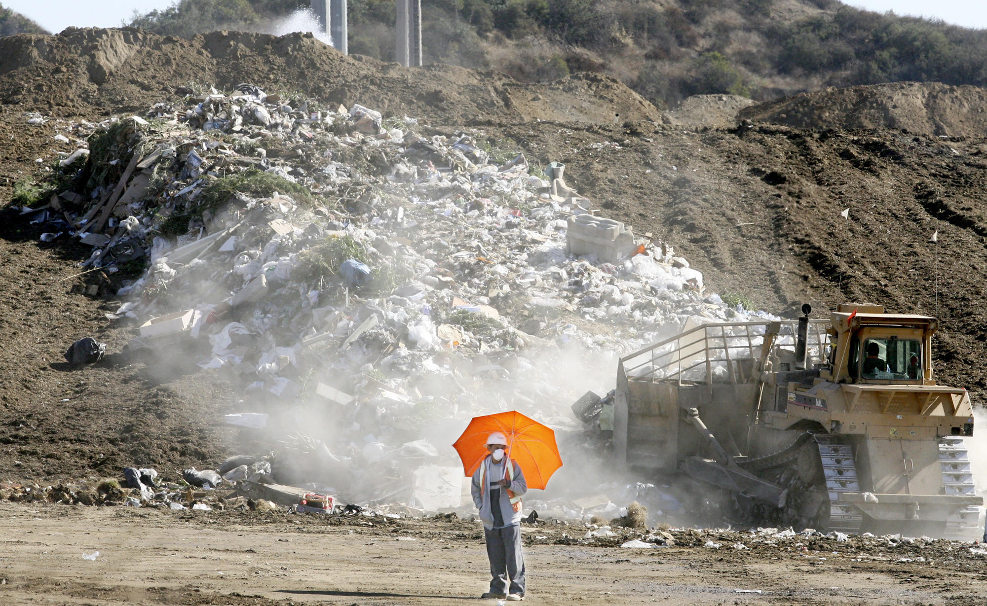 A worker keeps an eye on incoming vehicles while a bulldozer works trash into the Scholl Canyon landfill on Saturday, October 25, 2008.