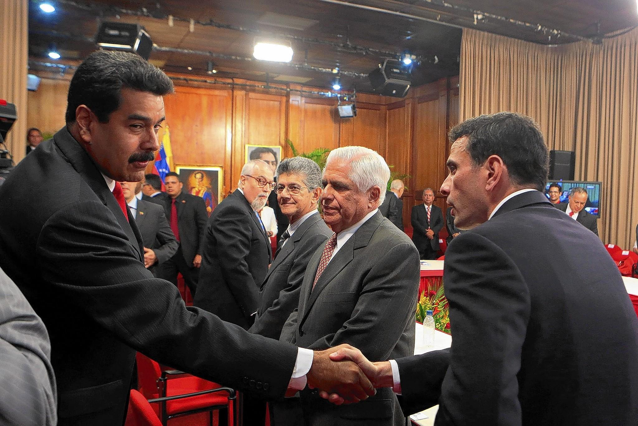 Venezuelan President Nicolas Maduro, left, greets opposition leader Henrique Capriles before a meeting at the Miraflores presidential palace in Caracas.