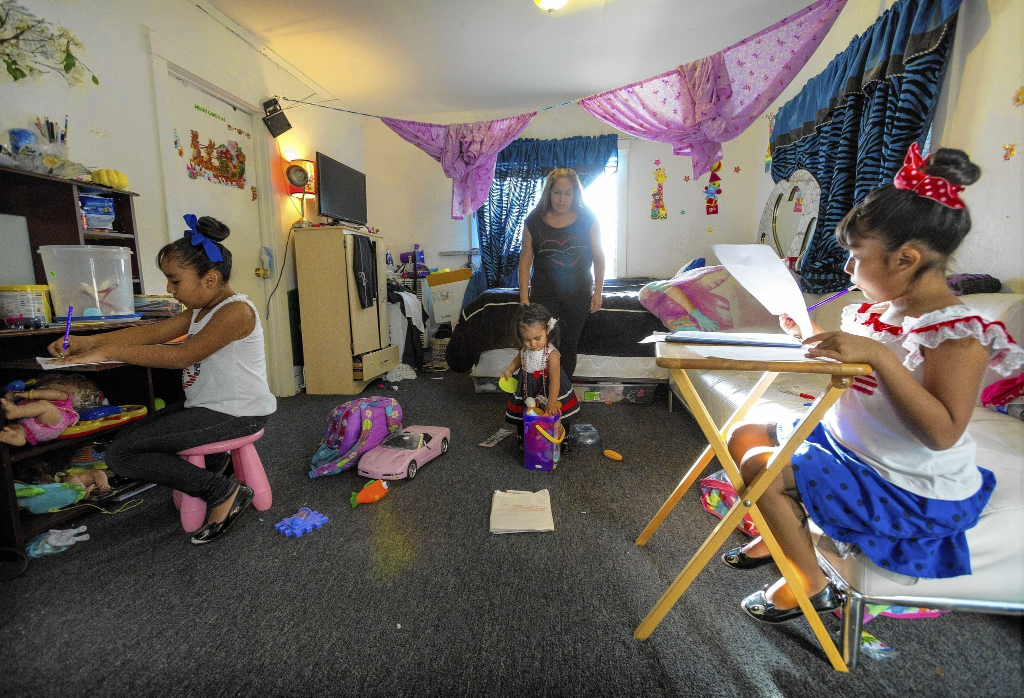 Sisters Ashley Orosco, left, and Lindsay study as their mom, Melina Vasquez, cares for Alexa in a rent-controlled Echo Park complex where all residents are being evicted.