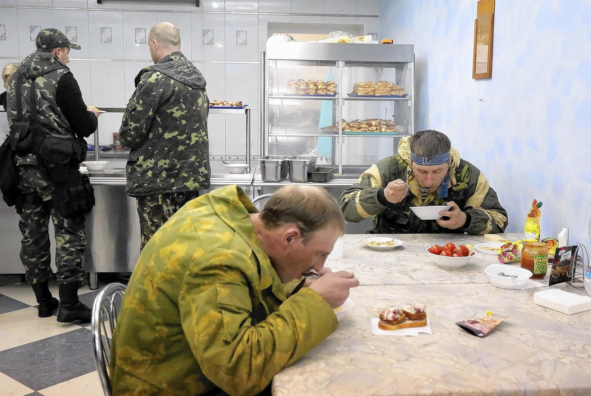 Pro-Russian protesters eat lunch in a cafeteria at the occupied security service building in Lugansk, Ukraine.