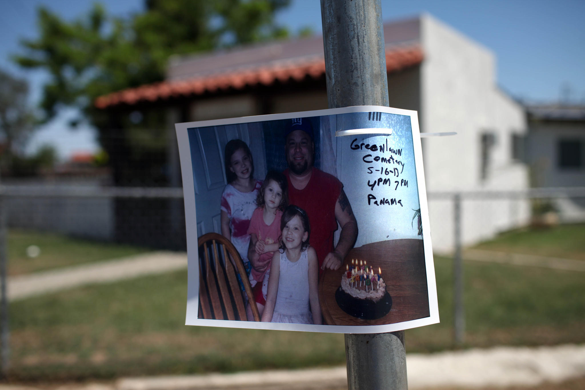 A photograph of David Sal Silva and his children was posted on a pole at the site of his beating last year. The date and time of a wake is written across it.