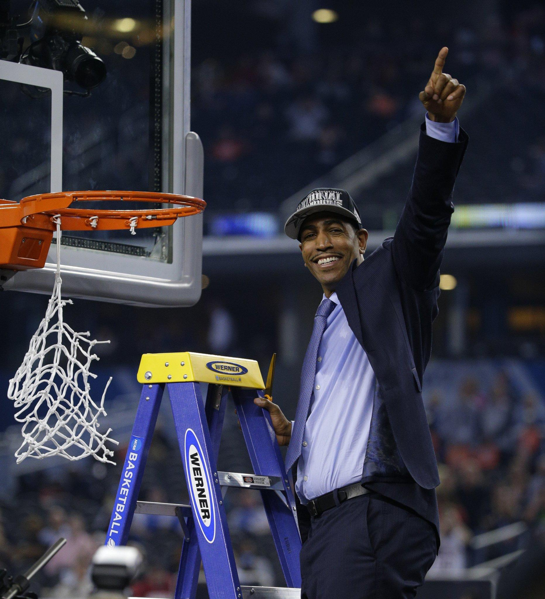Connecticut Huskies head coach Kevin Ollie goes up to cut the net as the Connecticut Huskies beat the Kentucky Wildcats 60-54 in the NCAA Final Four championship game at AT&T Stadium in Arlington, Texas, Monday, April 7, 2014. (Mark Cornelison/Lexington Herald-Leader/MCT)