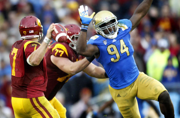 Bruins defensive end Owamagbe Odighizuwa (94) pressures USC quarterback Matt Barkley during their annual rivalry game two seasons ago.