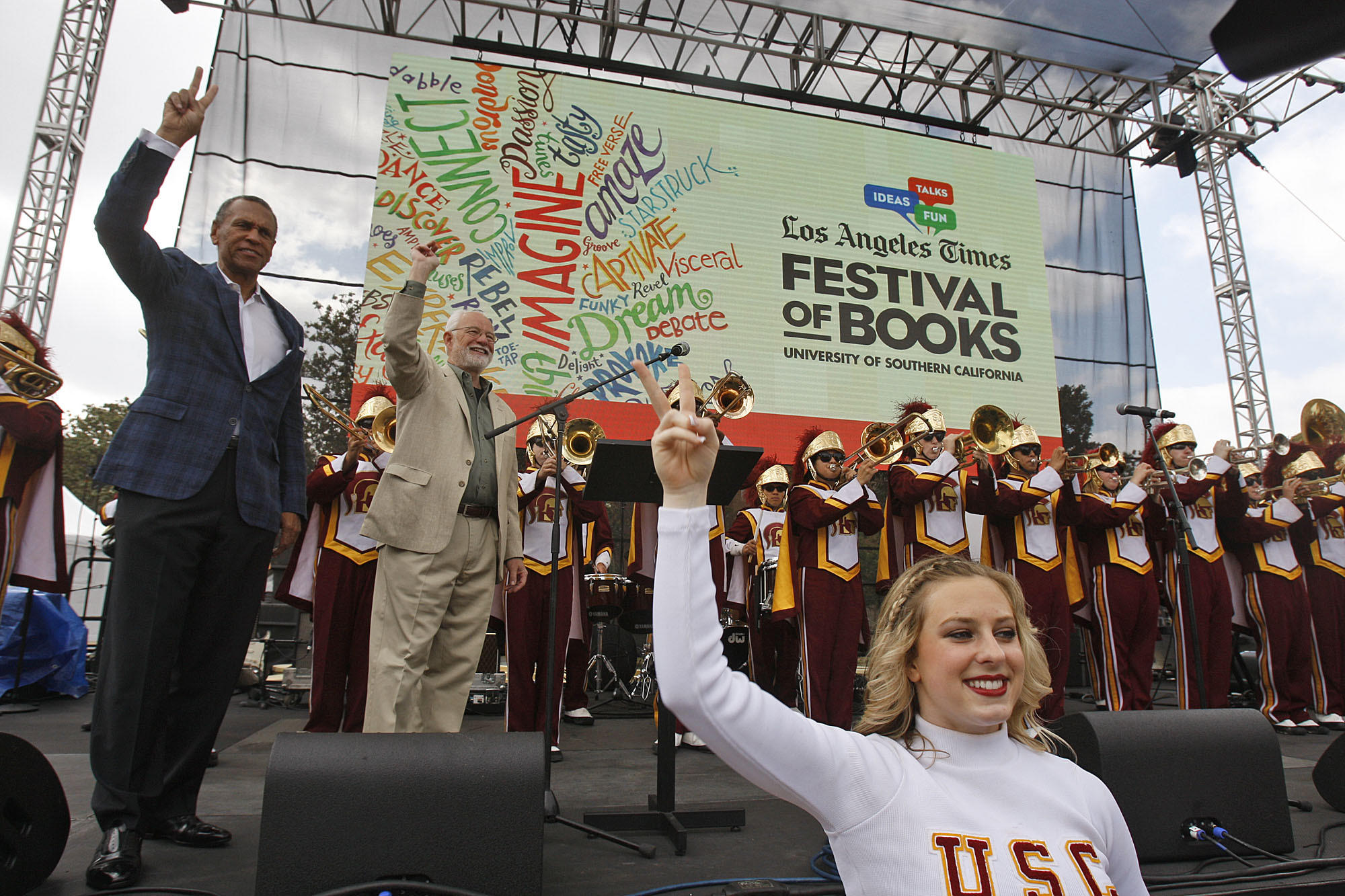Thomas Sayles of USC, left, and Times Publisher Eddy Hartenstein join the USC band and cheerleaders at the kickoff of the L.A. Times Festival of Books on Saturday on the USC campus.