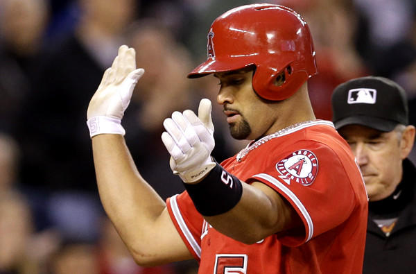 Angels first baseman Albert Pujols celebrates at home plate after hitting a home run against the Mariners on Wednesday in Seattle.