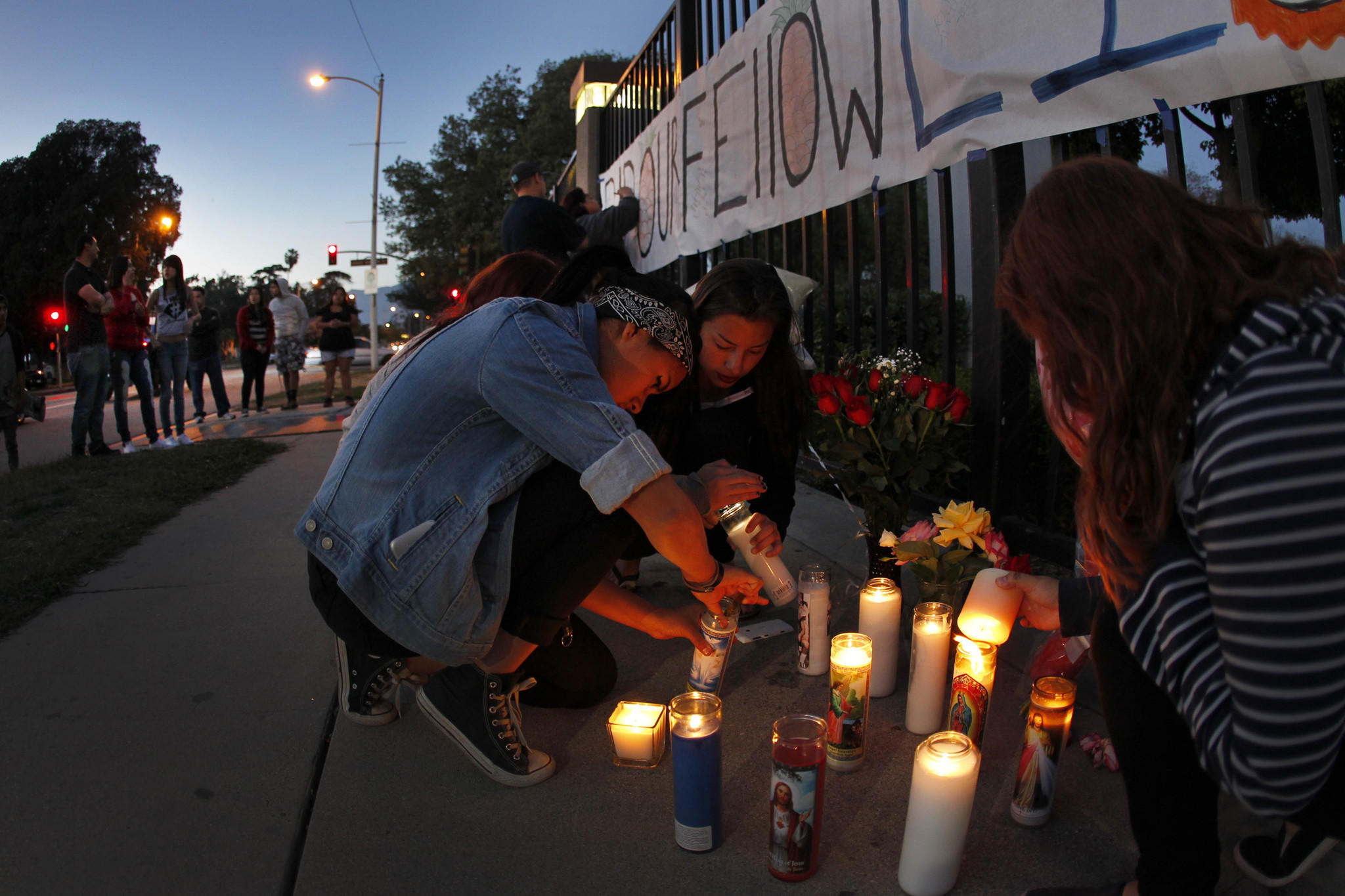 El Monte High School students light candles in front of the school at a memorial to Adrian Castro, a senior at the school killed Thursday in a Northern California bus crash.