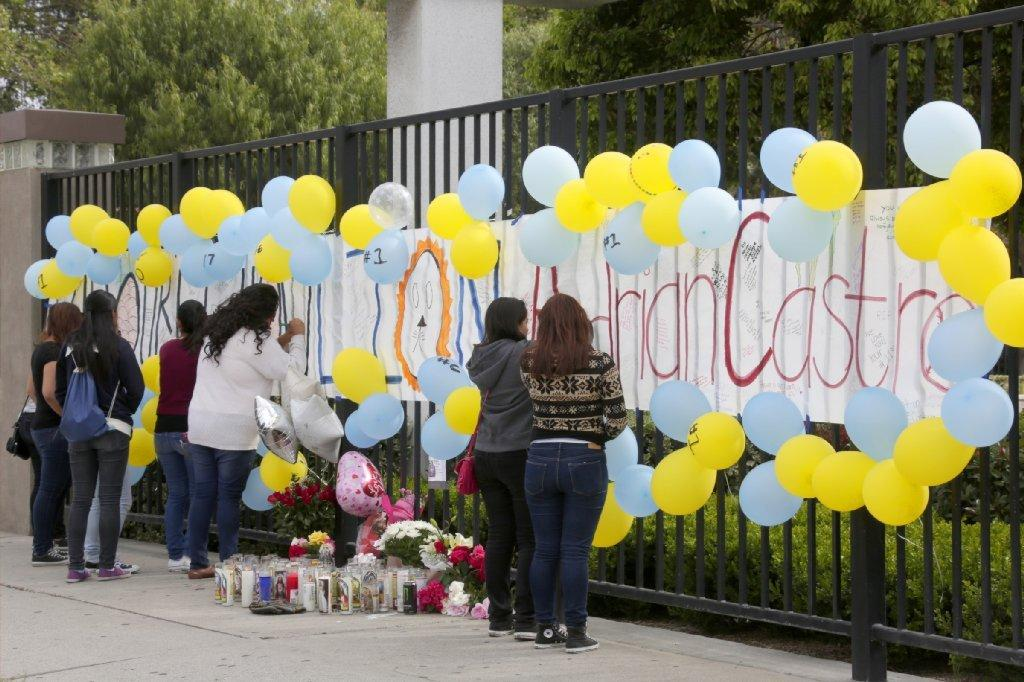 A group of students gather at El Monte High School on Saturday to create a memorial in honor of Adrian Castro, a student who was among those killed in a tour bus crash Thursday in Northern California.