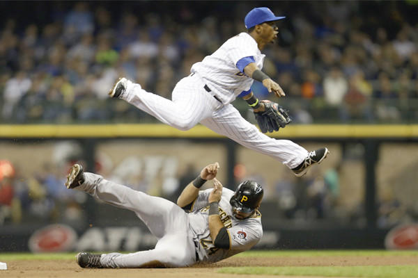 Milwaukee's Jean Segura urns the double play as Pittburgh's Pedro Alvarez slides into second base April 12 at Miller Park.