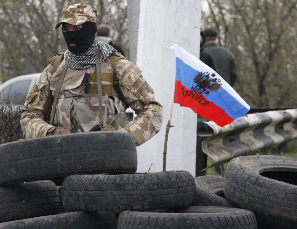 An armed pro-Russia activist guards a checkpoint on the Kharkiv-Donetsk road near the entrance to the eastern Ukrainian city of Slavyansk.