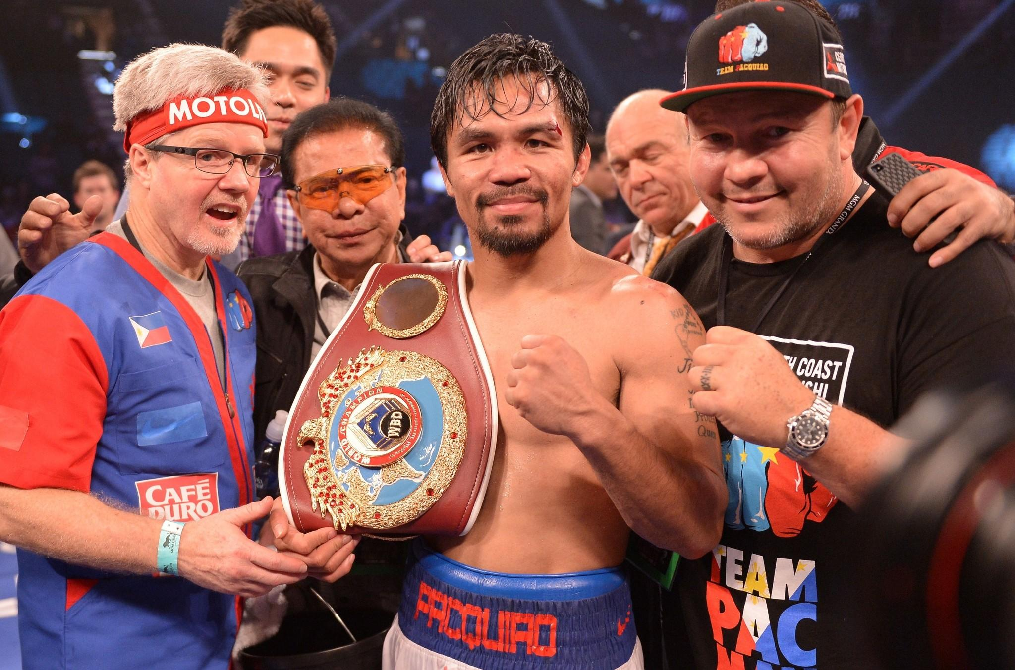 Manny Pacquiao shows off the WBO welterweight belt he won by defeating Timothy Bradley by unanimous decision.