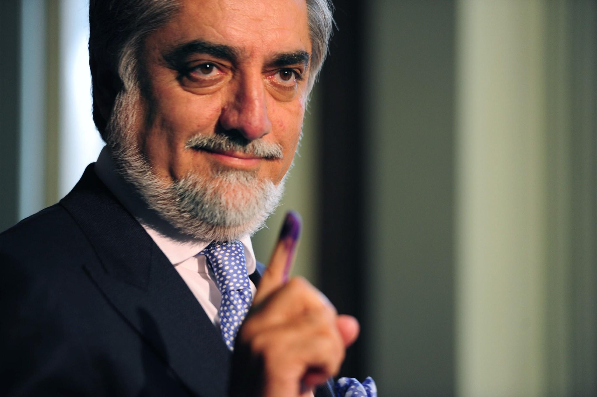 Afghan presidential candidate Abdullah Abdullah shows his inked finger as he casts his vote at a local polling station in Kabul.