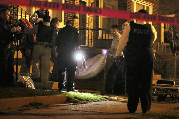 A body is removed from the scene after a man was shot and killed in the 3000 block of West 53rd Place in Chicago.