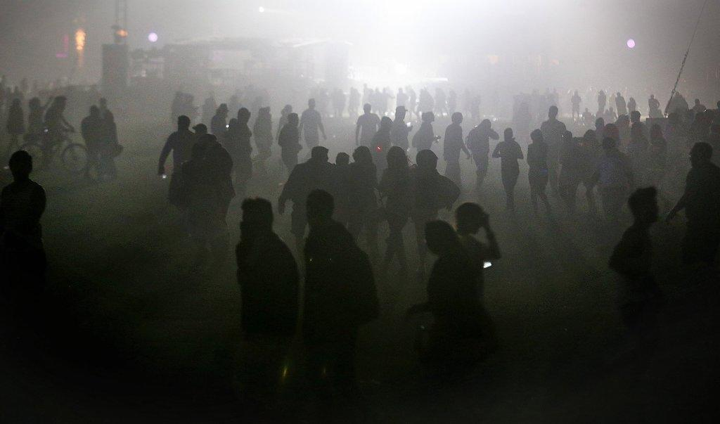Patrons trudge through a haze of sand and dust during high winds Saturday night at the Coachella Valley Music and Arts Festival in Indio.