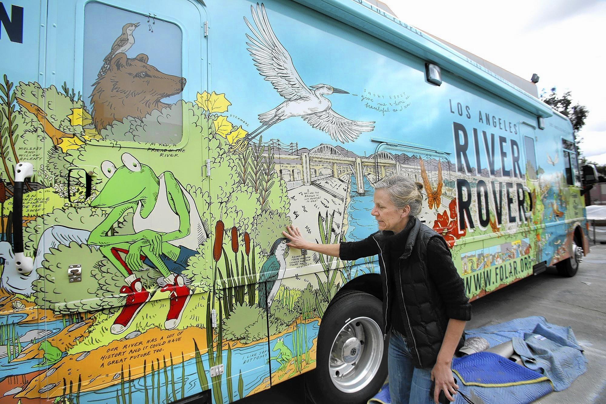 "Starting in May, the River Rover, festooned with splashy exterior renderings of riverscapes past, present and future — and amphibian mascot ""Froggy"" — will become a familiar sight at the 120 schools within a mile of the L.A. river. Above, artist Christian Kasperkovitz next to artwork she designed on the Rover's exterior."