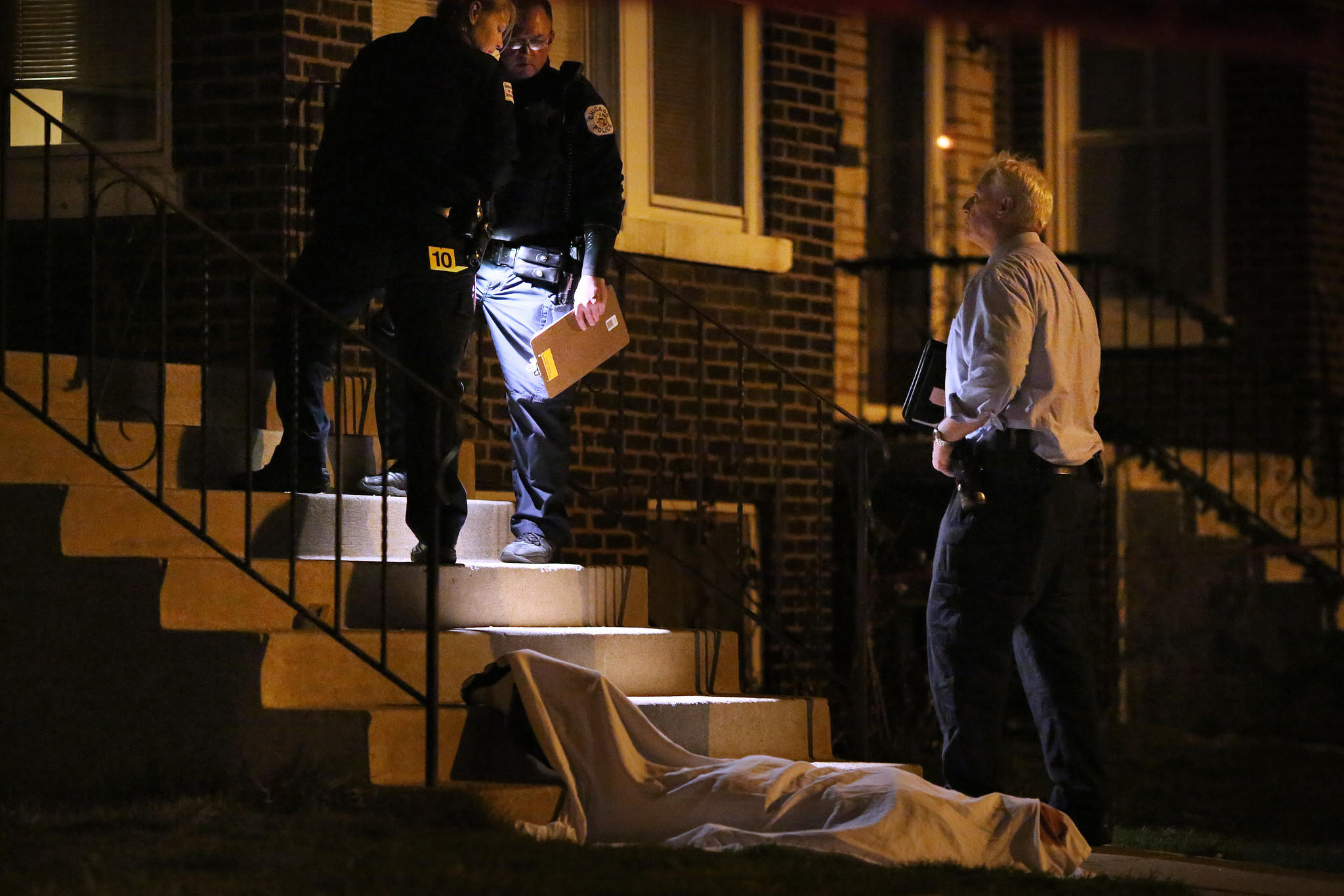 Police confer near the scene after a man was shot and killed Sunday, April 13, 2014 in the 3000 block of West 53rd Place in Chicago.