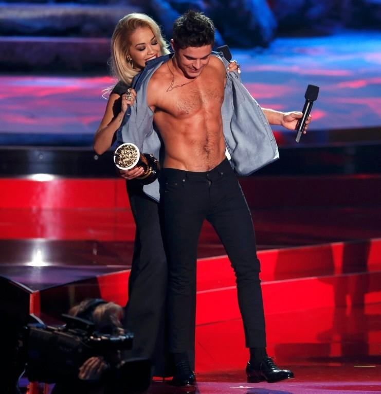 "Rita Ora rips open Zac Efron's shirt Sunday as he accepts the award for best shirtless performance for ""That Awkward Moment"" at the 2014 MTV Movie Awards in Los Angeles."