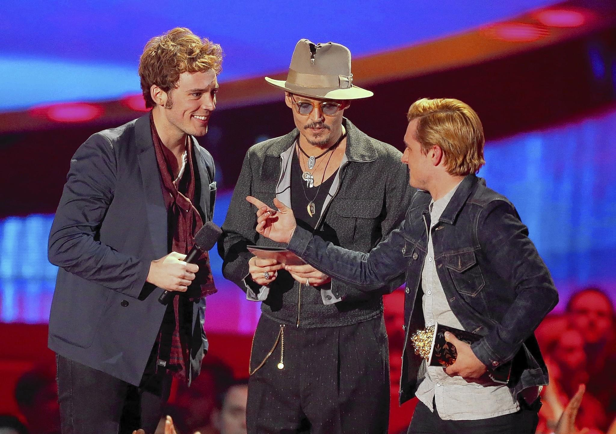 """Actors Sam Claflin, left, and Josh Hutcherson, right, accept the movie of the year award for """"The Hunger Games: Catching Fire"""" from actor Johnny Depp at the 2014 MTV Movie Awards at Nokia Theatre L.A. Live on April 13, 2014, in Los Angeles."""