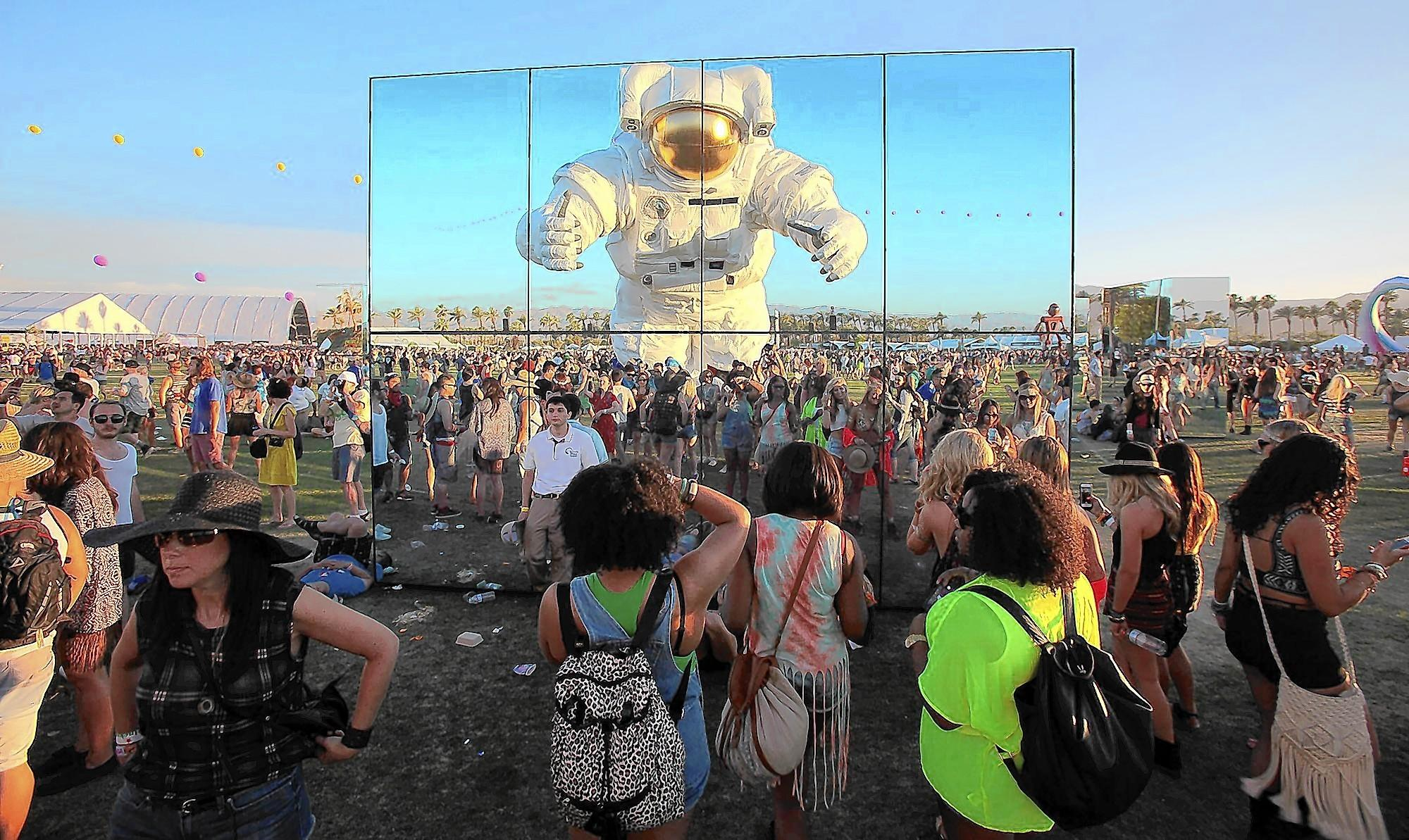 "A nearly 40-foot-tall astronaut ""Escape Velocity"" by Poetic Kinetics, an L.A.-based art collective, is reflected in ""Reflection Fields"" by Phillip K. Smith as it roams through the crowd at the Coachella Valley Music and Arts Festival April 11, 2014, in Indio."