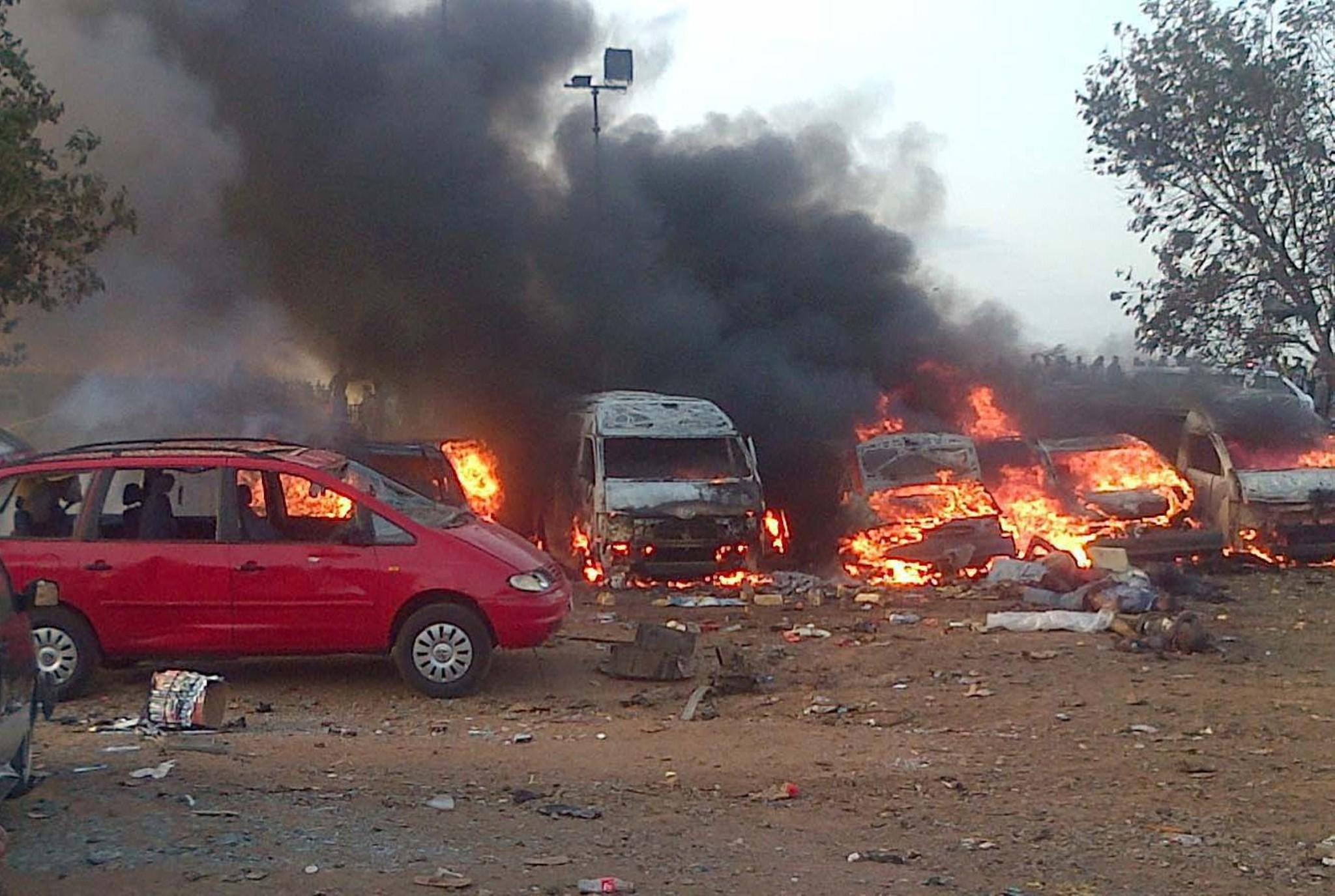 Vehicles burn after a bombing at a bus station in the Nigerian city of Abuja.