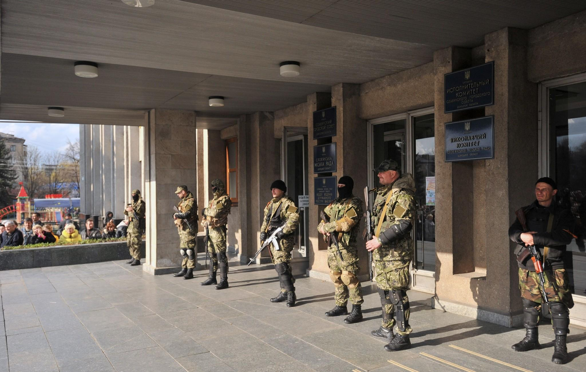 Armed pro-Russia militants stand guard outside the regional administration building in the eastern Ukrainian city of Slavyansk on Monday. Local police reportedly failed to support the Ukrainian government's ultimatum to pro-Kremlin militias to lay down their weapons, and the gunmen have gone on to seize more facilities in eastern Ukraine.