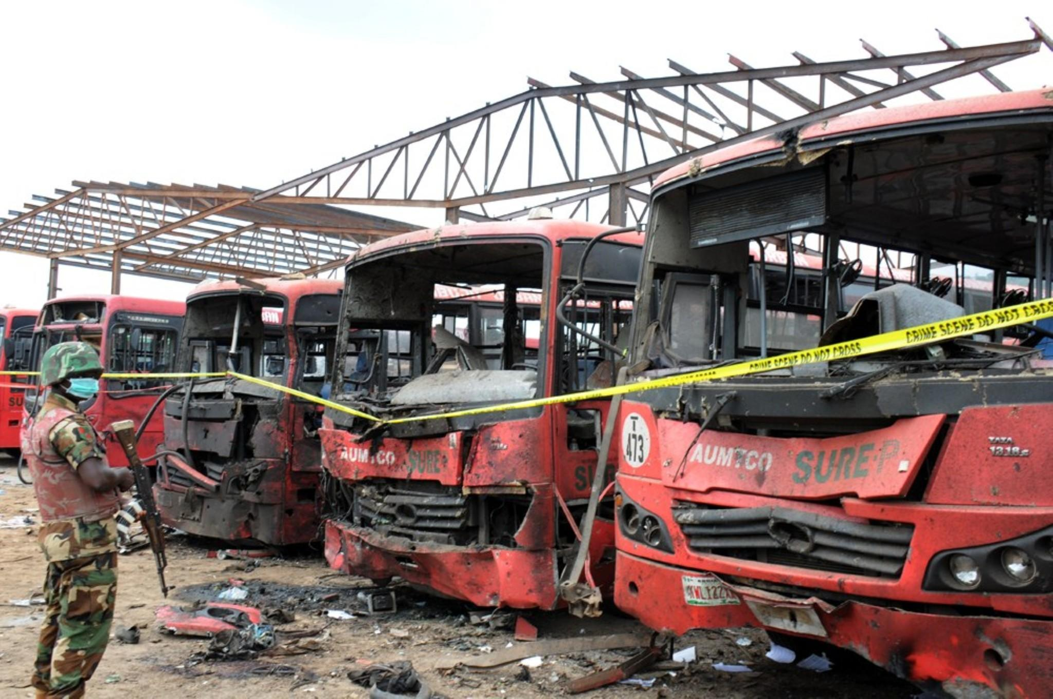 A soldier stands guard in front of burnt buses after an explosion outside the Nigerian capital, Abuja.
