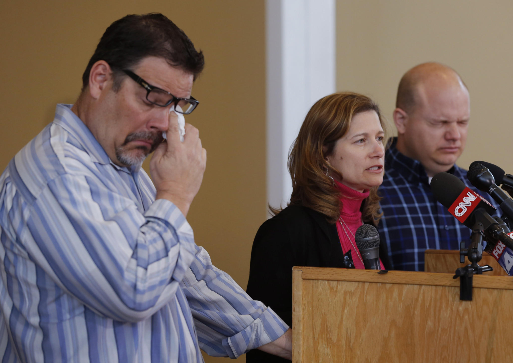 Will Corporon, left, and Tony Corporon, right, fight emotions while Mindy Losen talks about her son and father during a news conference at their church in Leawood, Kan.