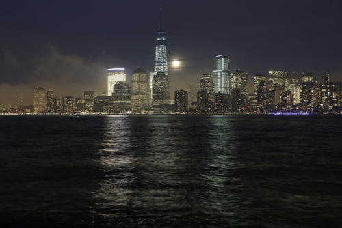 A full moon rises behind the skyline of Lower Manhattan and One World Trade Center in New York, January 15, 2014.