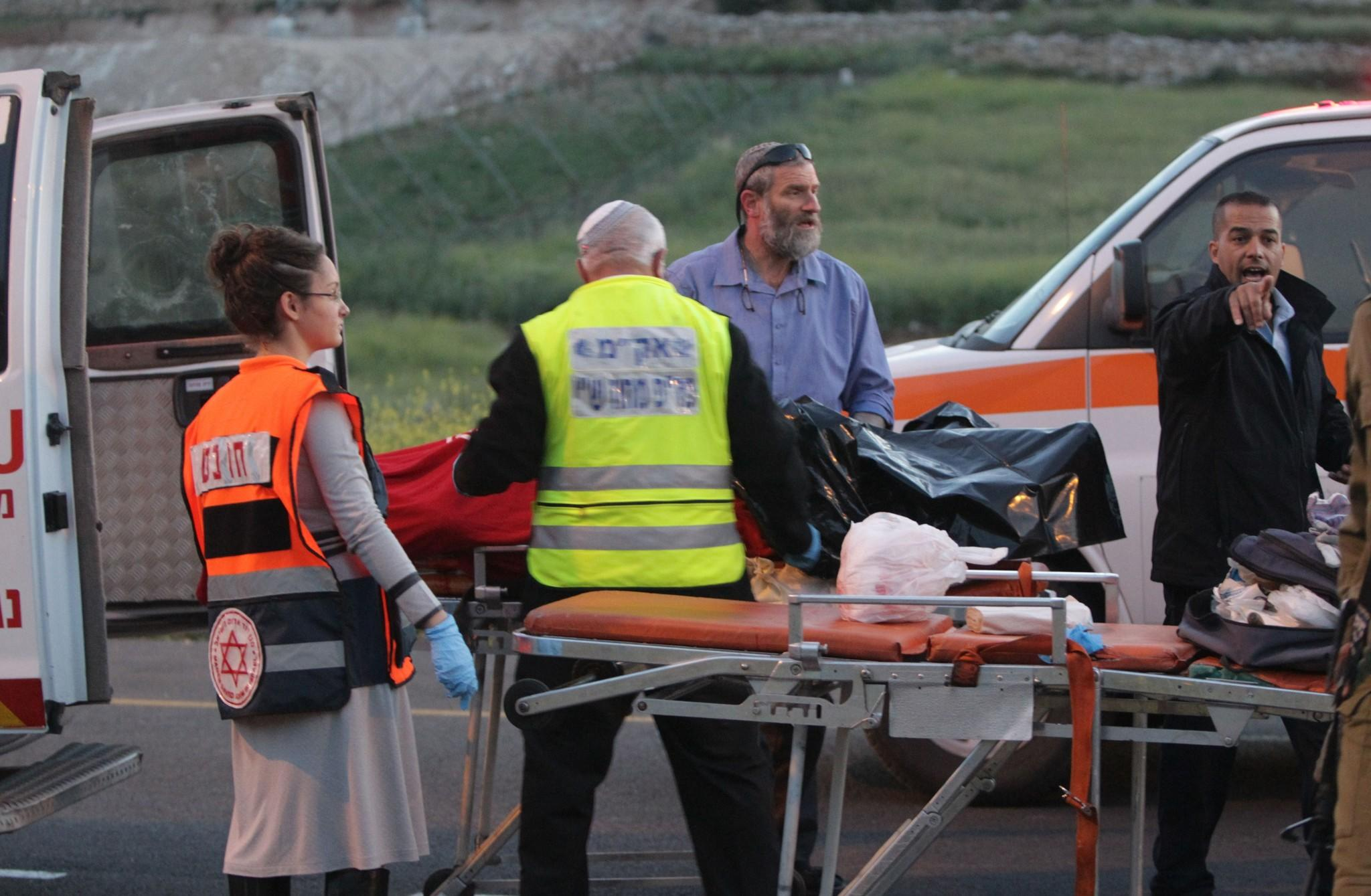 Israeli police and medical personnel load the body of an Israeli man into the back of an ambulance at the scene of a shooting near the southern West Bank city of Hebron.