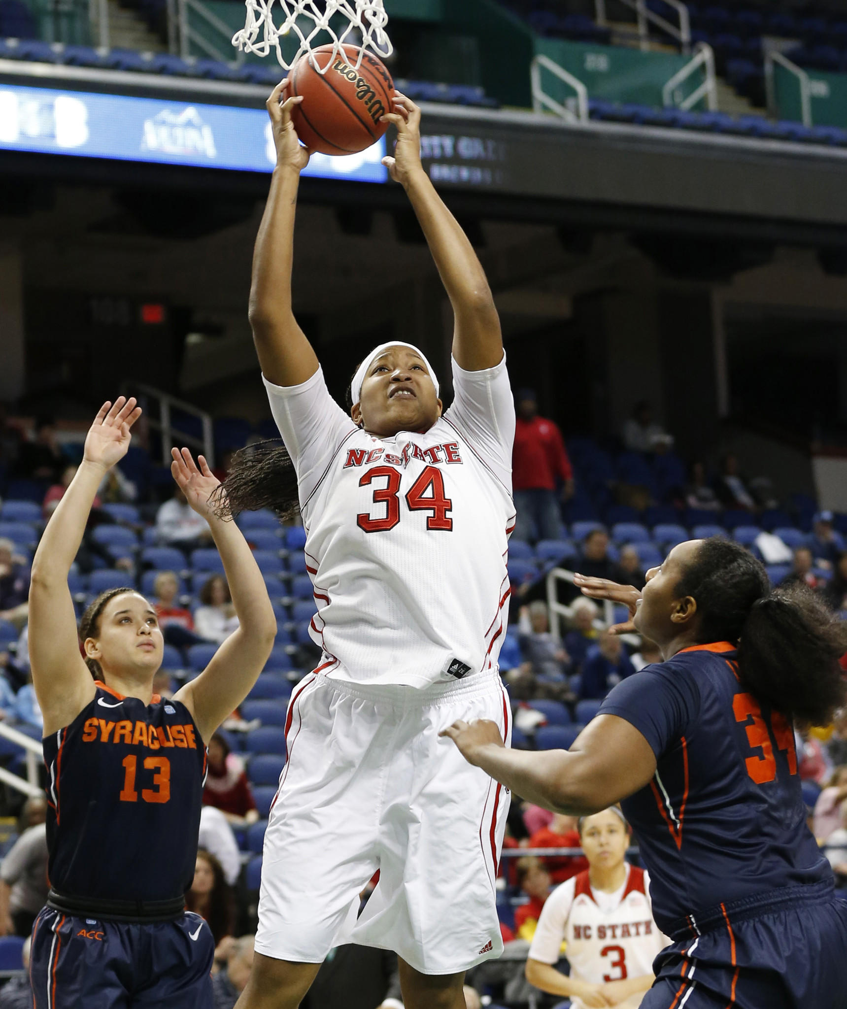 North Carolina State's Markeisha Gatling goes to the basket against Syracuse's Brianna Butler and Shakeya Leary at Greensboro Coliseum.