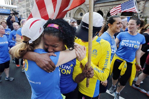 Rosa Evora, center, hugs a fellow participant in a cross-country relay that began in March in California and ended at the Boston Marathon finish line Sunday.