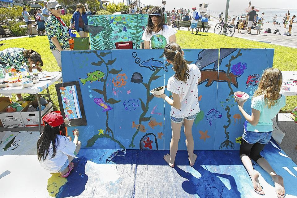 Children work on filling a kelp mural during Kelpfest 2013 at Main Beach in Laguna Beach.