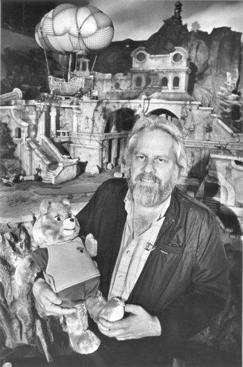 Ken Forsse holding the Teddy Ruxpin character in front of the set of the Hard to Find City, part of the adventures of the Ruxpin character being filmed at Renmar Studios in Hollywood.