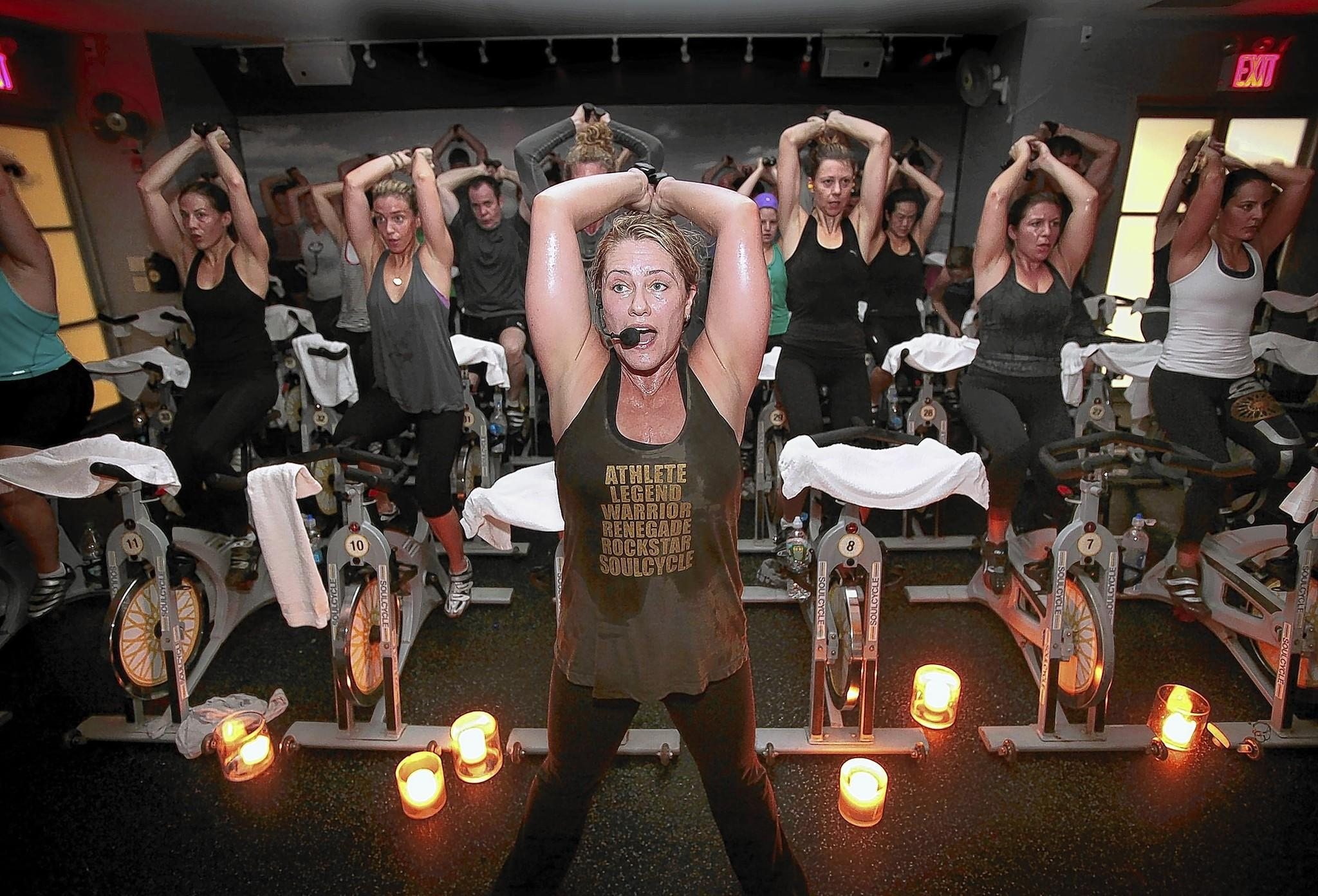 Instructor Janet Fitzgerald leads a class at SoulCycle in New York. Arm weights are a part of the class.