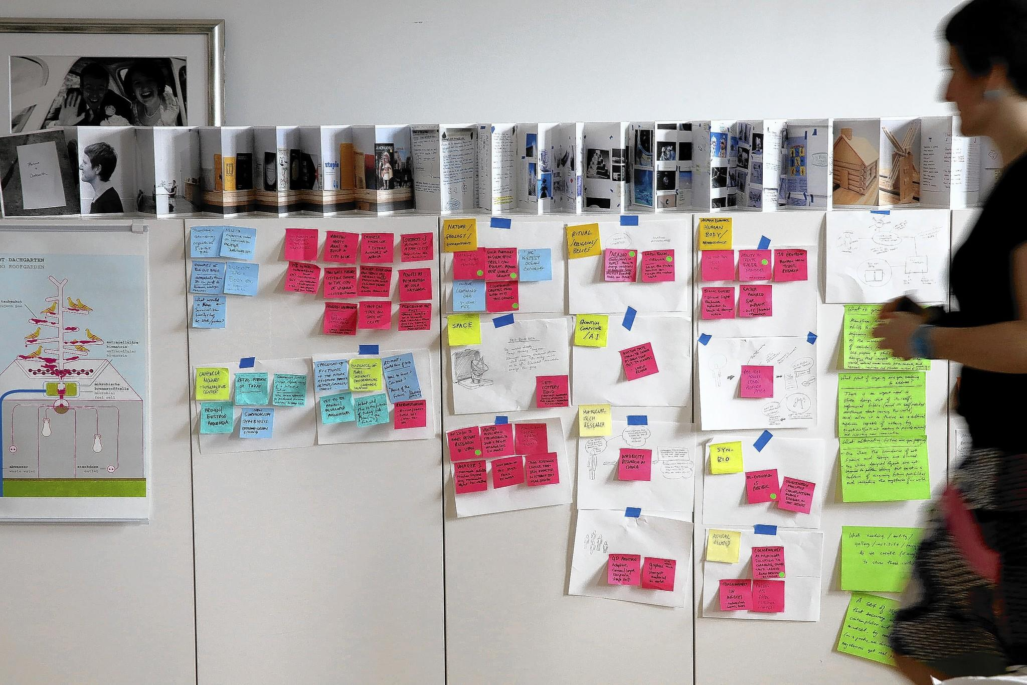 Speculative designer Jessica Charlesworth passes a display of sticky notes of various ideas, topics, and headlines used for brainstorming.