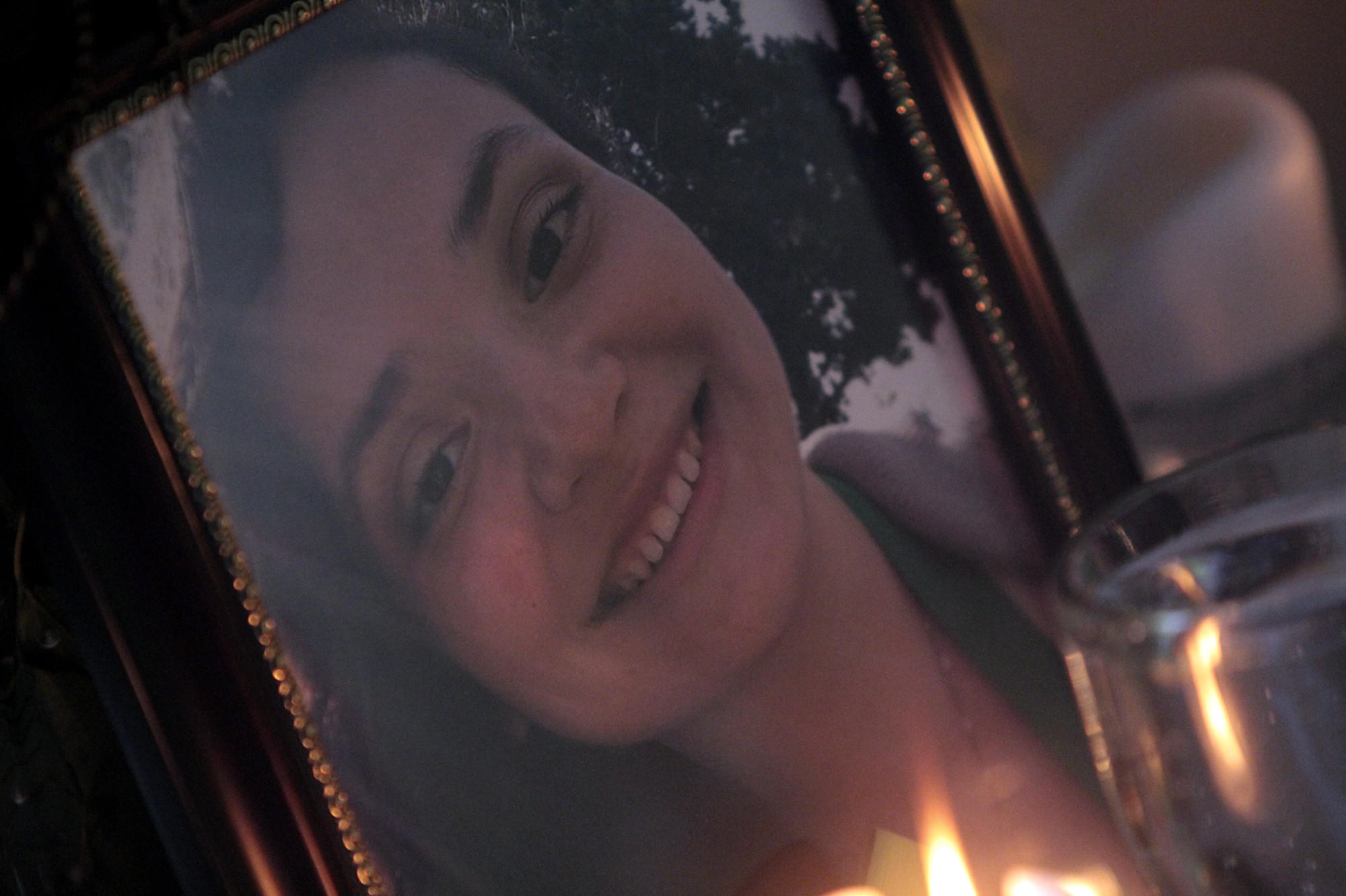 A candle burns next to a family photo of Jennifer Bonilla, the Dorsey High senior who was killed in last week's bus crash in Orland, Calif.