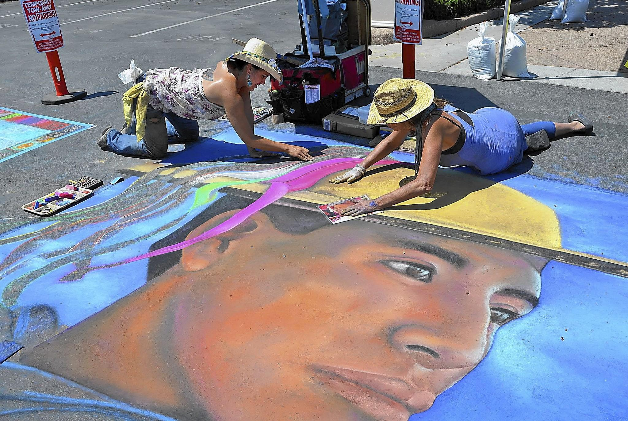 Cynthia Kostylo, left, and Raziah Roushan complete a portrait as part of the Strada Dell'Arte:Spectacular Chalk Murals during the Newport to Ensenada Race Kickoff Fiesta held Sunday in Balboa Village.
