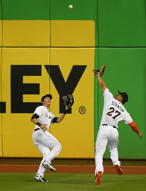 Christian Yelich #21 and Giancarlo Stanton #27 of the Miami Marlins chase down a fly ball during a game against the Washington Nationals at Marlins Park on April 14, 2014 in Miami, Florida.