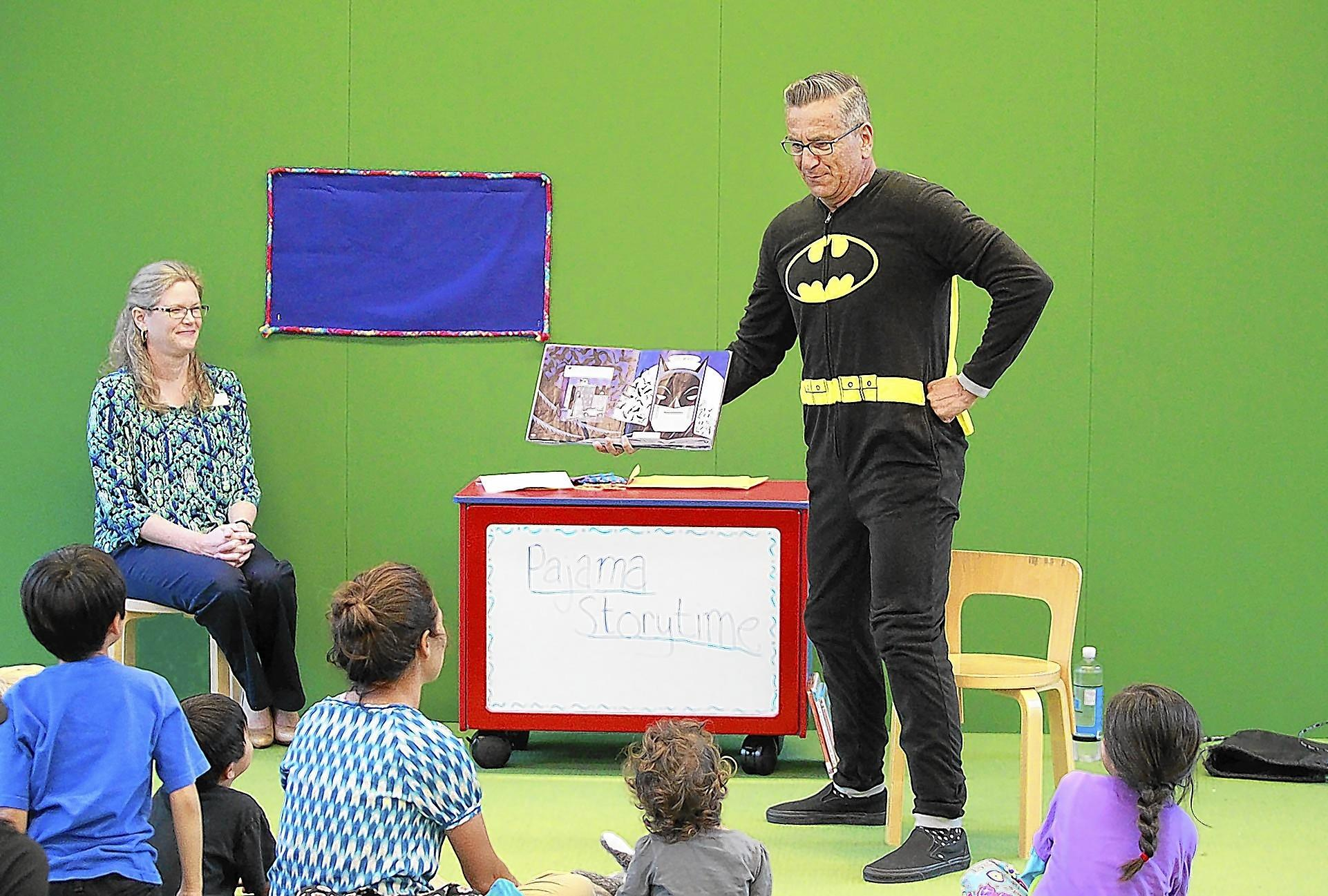 "Newport Beach councilman Tony Petros plays a convincing Batman as he volunteers to read ""Batman: Story of the Black Knight"" on Monday at the Newport Beach Central Library."
